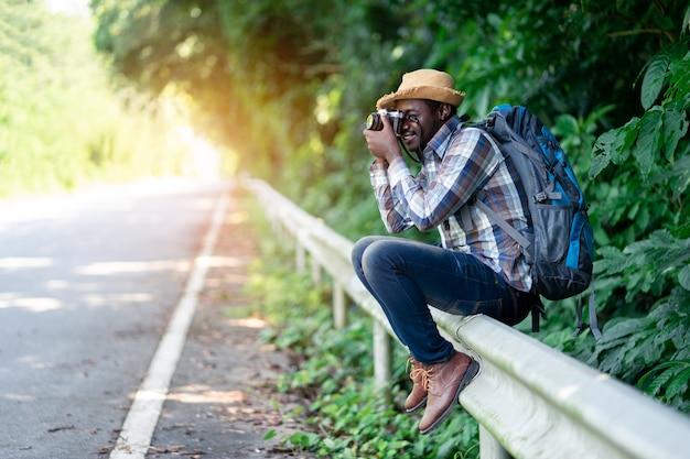 Homme africain transportant un sac à dos et tenant l'appareil photo du côté de la route