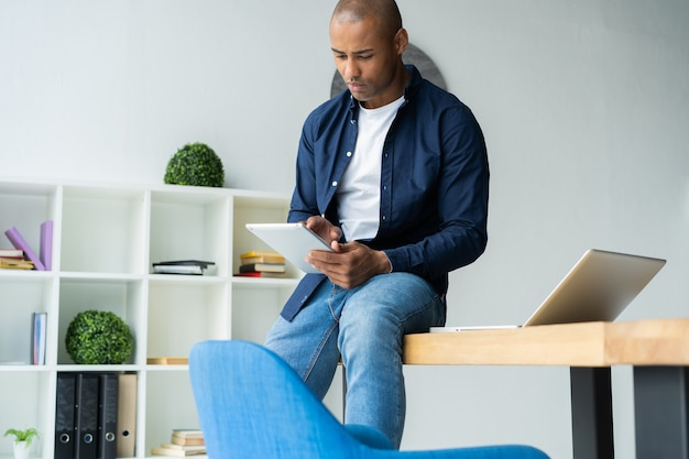 Homme africain utilisant sa tablette numérique alors qu'il était assis sur une table sur son lieu de travail