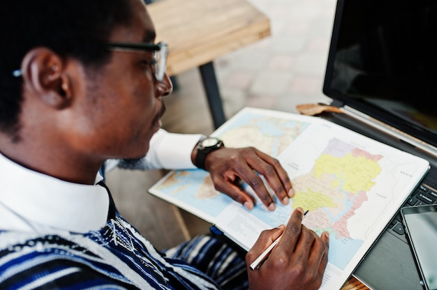 Homme africain en vêtements traditionnels et lunettes assis derrière un ordinateur portable au café en plein air et à la recherche sur la carte de l'afrique et du ghana à son ordinateur portable