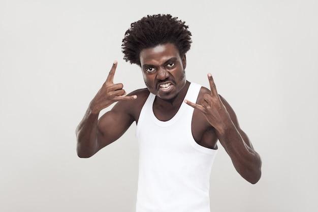 Homme afro agressif montrant le signe du rock, regardant la caméra. prise de vue en studio. fond gris