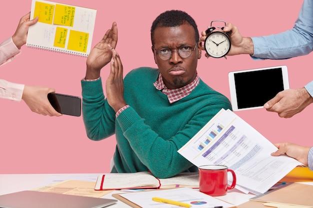 Homme afro-américain assis au bureau entouré de gadgets et de papiers