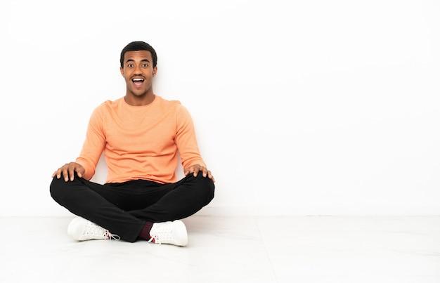 Homme afro-américain assis sur le sol sur fond de fond isolé avec une expression faciale surprise