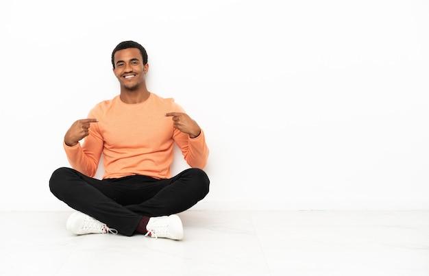 Homme afro-américain assis sur le sol sur fond de fond isolé fier et satisfait de lui-même