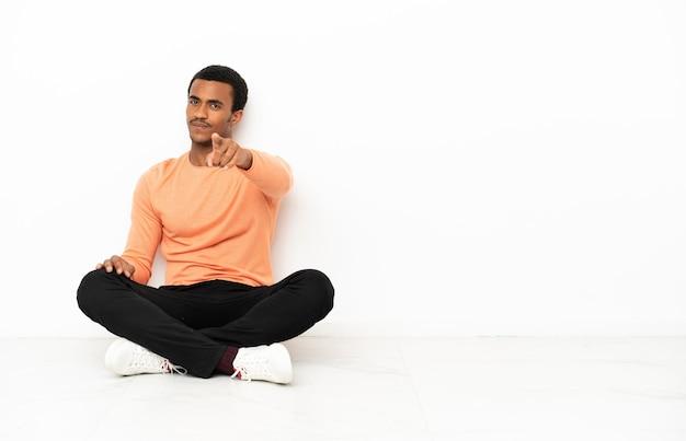 Un homme afro-américain assis sur le sol sur un fond isolé vous pointe du doigt avec une expression confiante