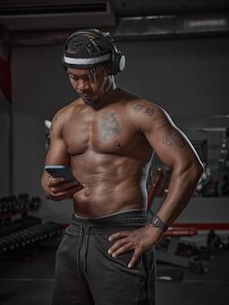 Homme afro-américain athlétique dans des écouteurs avec téléphone à l'aide d'une application sportive pendant l'entraînement en salle de sport