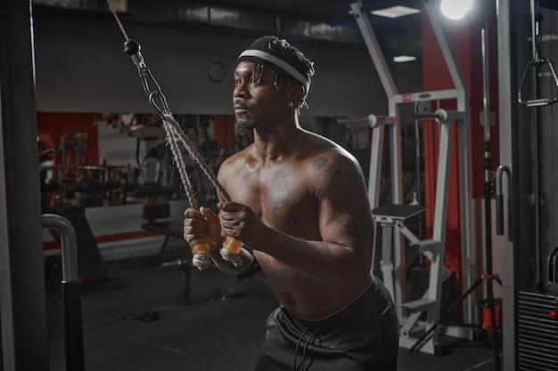 Homme afro-américain athlétique musclé s'entraînant dans la salle de gym musculation entraînement de force sportive