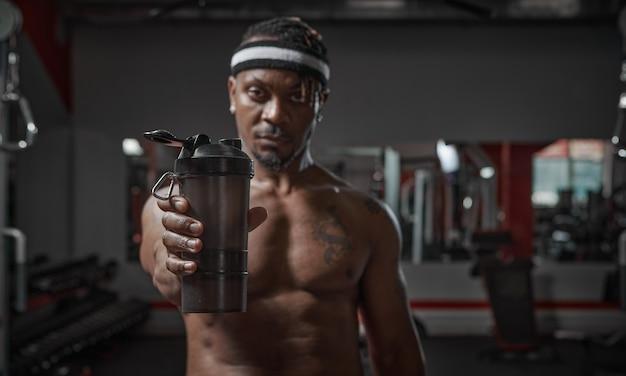 Homme afro-américain athlétique avec torse nu montrant un verre de sport avec de l'eau ou une nutrition sportive