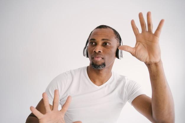 Homme afro-américain attrayant, écouter de la musique avec des écouteurs bluetooth.