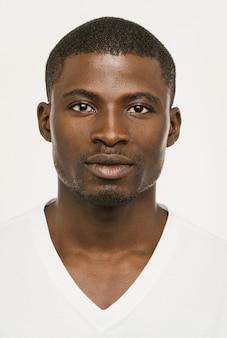 Homme afro-américain attrayant regardant sérieusement la caméra, gars à la peau sombre dans un t-shirt blanc sur fond blanc