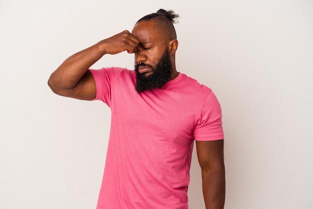Homme afro-américain avec barbe isolé sur fond rose ayant un mal de tête, touchant le devant du visage.