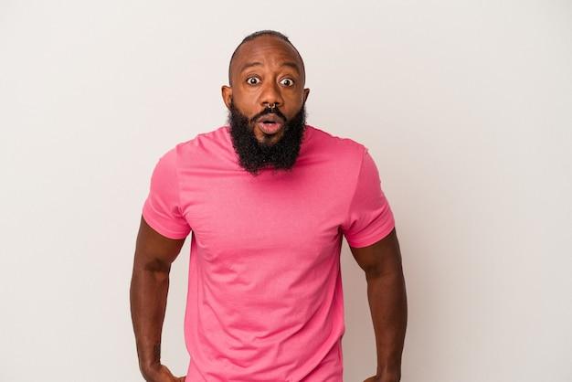 Homme afro-américain avec barbe isolé sur fond rose choqué à cause de quelque chose qu'elle a vu.