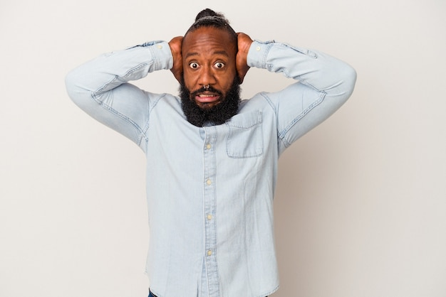 Homme afro-américain avec barbe isolé sur fond rose criant de rage.