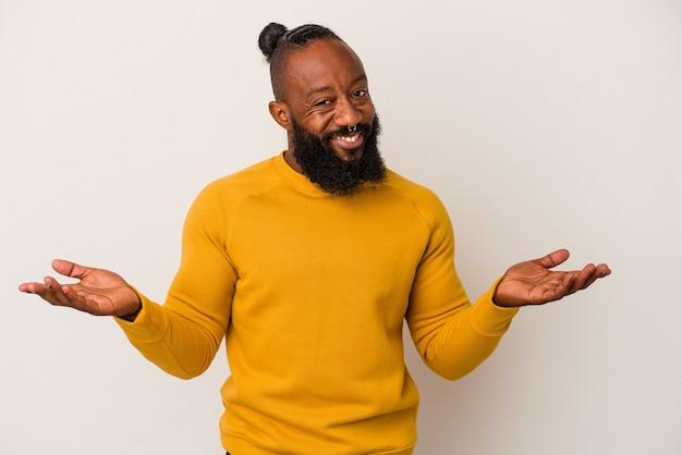 L'homme afro-américain à la barbe isolé sur fond rose fait de l'échelle avec les bras, se sent heureux et confiant.