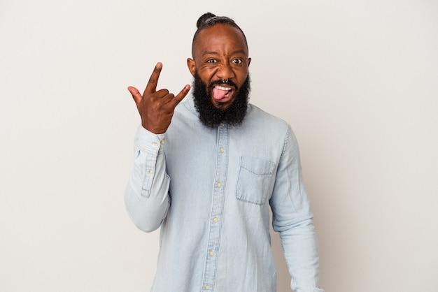 Homme afro-américain avec barbe isolé sur fond rose montrant un geste rock avec les doigts