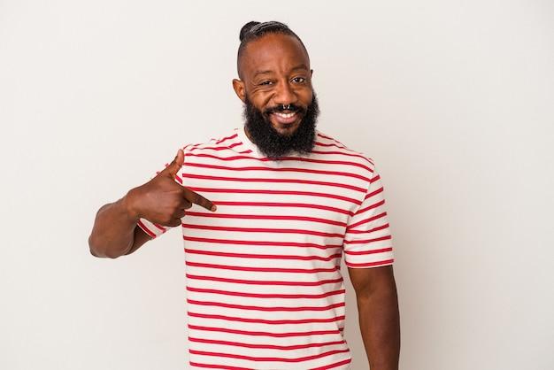 Homme afro-américain avec barbe isolé sur fond rose personne pointant à la main vers un espace de copie de chemise, fier et confiant