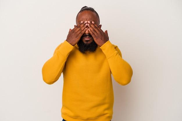 Homme afro-américain avec barbe isolé sur fond rose peur couvrant les yeux avec les mains.