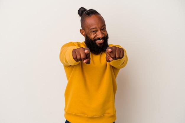 Homme afro-américain avec barbe isolé sur fond rose pointant vers l'avant avec les doigts.