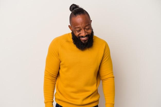 Homme afro-américain avec barbe isolé sur fond rose rit et ferme les yeux, se sent détendu et heureux.