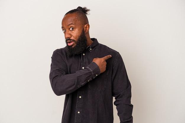 Homme afro-américain avec barbe isolé sur fond rose souriant et pointant de côté, montrant quelque chose dans un espace vide.