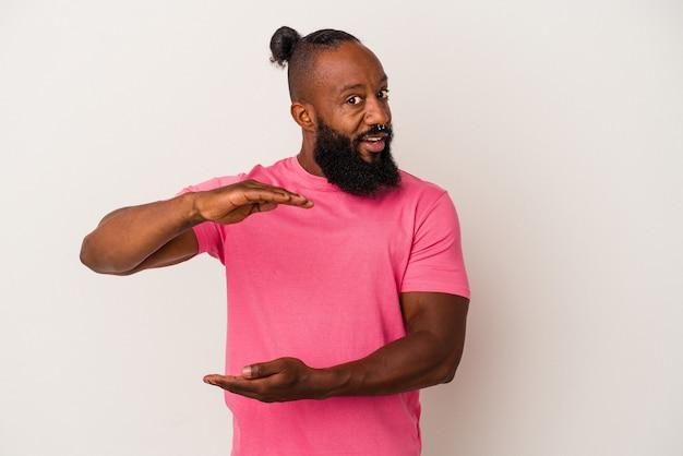 Homme afro-américain avec barbe isolé sur fond rose tenant quelque chose avec les deux mains, présentation du produit.