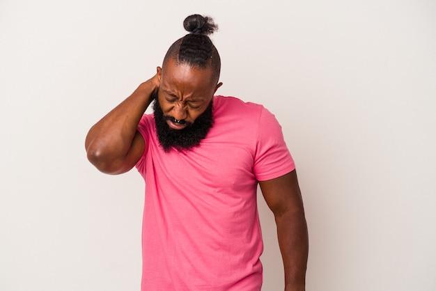 Homme afro-américain avec barbe isolé sur mur rose ayant une douleur au cou due au stress, en le massant et en le touchant avec la main.