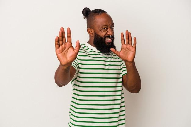 Homme afro-américain avec barbe isolé sur mur rose choqué en raison d'un danger imminent