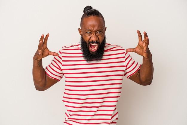 Homme afro-américain avec barbe isolé sur mur rose criant de rage.