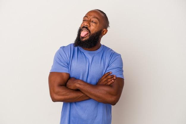 Homme afro-américain avec barbe isolé sur mur rose drôle et sympathique qui sort la langue.