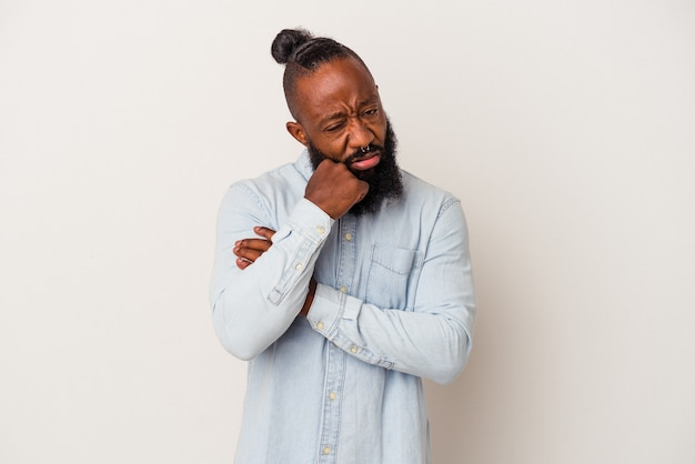 Homme afro-américain avec barbe isolé sur mur rose fatigué d'une tâche répétitive.