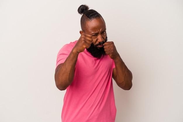 Homme afro-américain avec barbe isolé sur mur rose jetant un coup de poing, colère, combat à cause d'une dispute, boxe.