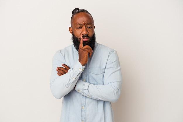 Homme afro-américain avec barbe isolé sur mur rose malheureux à la recherche d'une expression sarcastique.