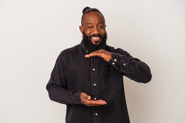 Homme afro-américain avec barbe isolé sur mur rose tenant quelque chose avec les deux mains, présentation du produit.