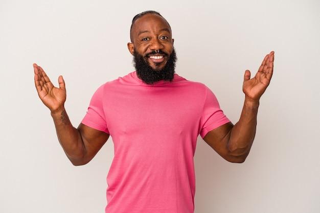 Homme afro-américain avec barbe isolé sur mur rose tenant quelque chose de petit avec les index, souriant et confiant.