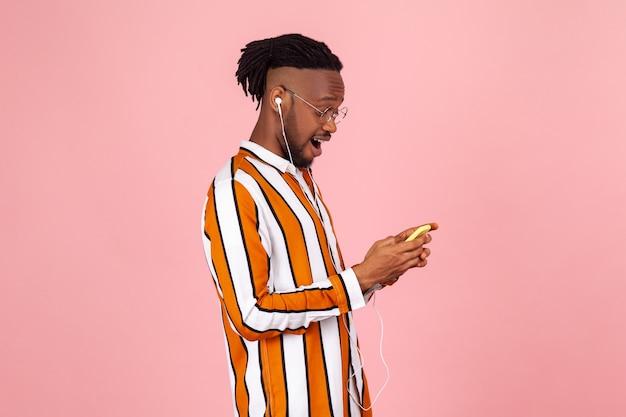 Homme afro-américain barbu discutant avec un smartphone et écoutant de la musique ou parlant avec des écouteurs