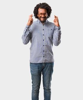 Homme afro-américain de belles affaires croise ses doigts, souhaite avoir de la chance pour l'avenir