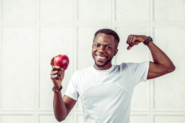 Homme afro-américain en bonne santé, tenant une pomme