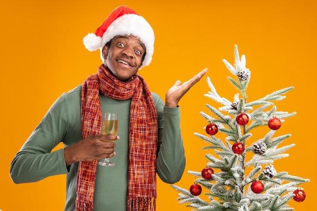 Homme afro-américain en bonnet de noel et écharpe autour du cou tenant un verre de champagne souriant joyeusement avec bras levé debout à côté d'un arbre de noël sur un mur orange