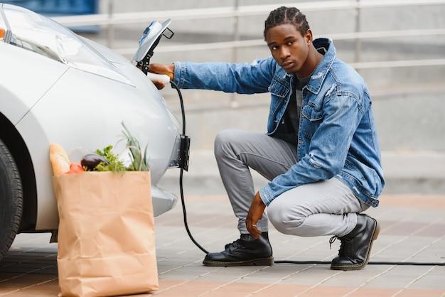 Homme afro-américain chargeant sa voiture électrique.