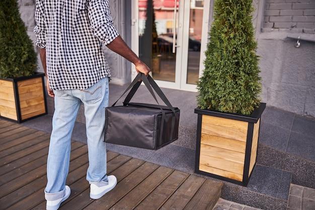 Homme afro-américain en chemise à carreaux et jean bleu tenant un sac d'emballage thermique isolé
