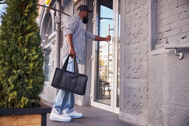Homme afro-américain en chemise à carreaux tenant un sac d'emballage thermique isolé lors de la livraison de la commande