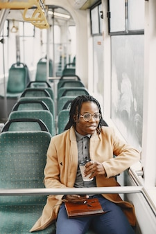 Homme afro-américain à cheval dans le bus de la ville. guy dans un manteau marron. homme avec du café.
