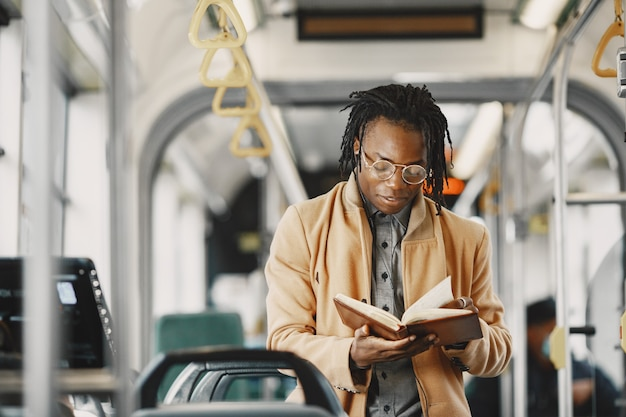 Homme afro-américain à cheval dans le bus de la ville. guy dans un manteau marron. homme avec ordinateur portable.