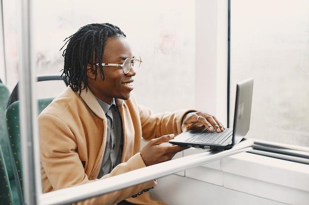 Homme afro-américain à cheval dans le bus de la ville. guy dans un manteau marron. homme avec un ordinateur portable.