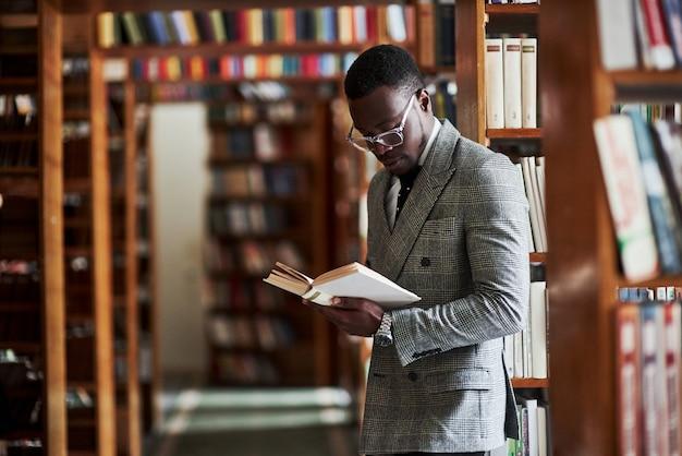 Un homme afro-américain dans un costume d'affaires debout dans une bibliothèque dans la salle de lecture.