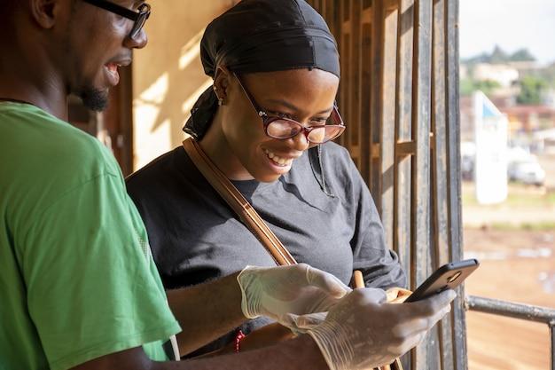 Homme afro-américain dans des gants en latex montrant quelque chose au téléphone à une femme afro-américaine