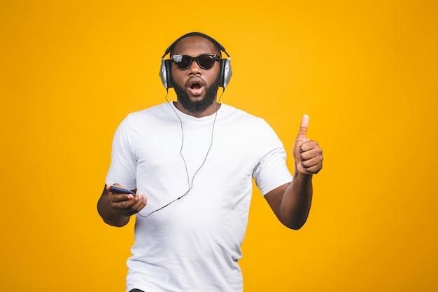 Homme afro-américain dans des vêtements décontractés et des écouteurs, écouter de la musique et danser. pouces vers le haut.