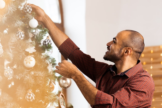 Homme afro-américain décorant le sapin de noël à la maison