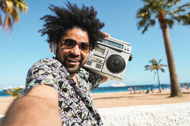 Homme afro-américain, écouter de la musique avec stéréo vintage boombox en plein air avec plage
