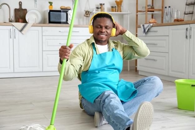 Homme afro-américain, écouter de la musique tout en nettoyant la cuisine