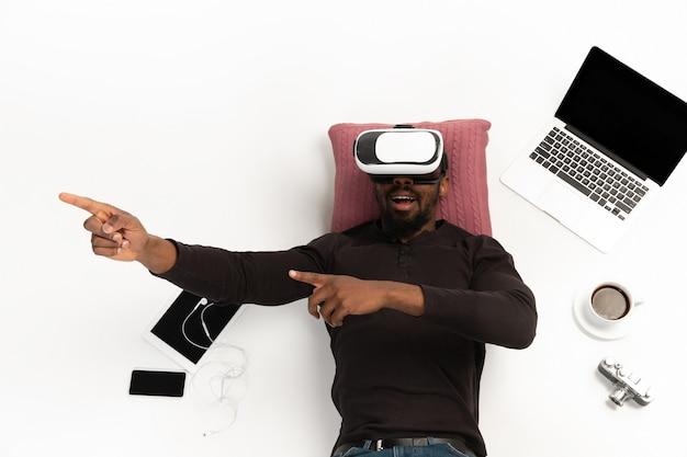 Homme afro-américain émotionnel à l'aide de casque vr entouré de gadgets isolés sur fond de studio blanc, technologies. jeu émotionnel
